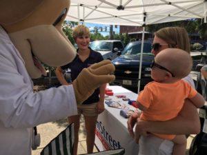 Mascot of MainStreet Family Urgent Care waves at a baby at the Eufaula Farmers Market