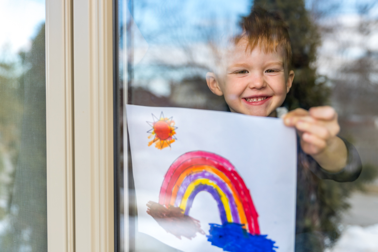 child holding up picture of rainbow to window