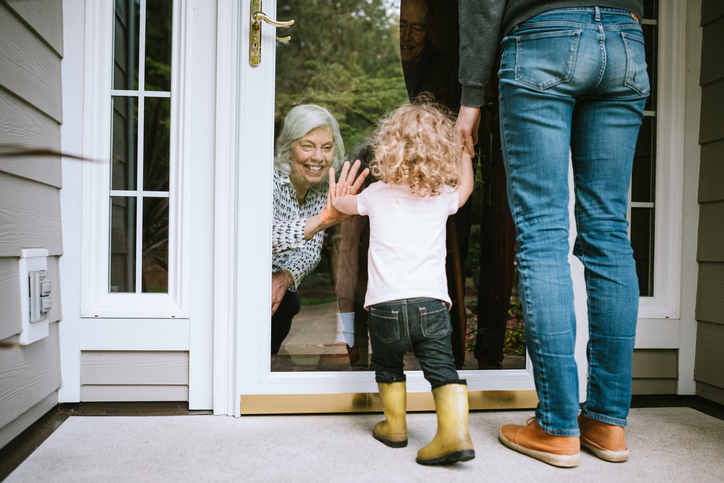 A mother stands with her daughter, visiting senior parents but observing social distancing with a glass door between them. The granddaughter puts her hand up to the glass, the grandfather and grandmother doing the same. A small connection in a time of separation during the Covid-19 pandemic.
