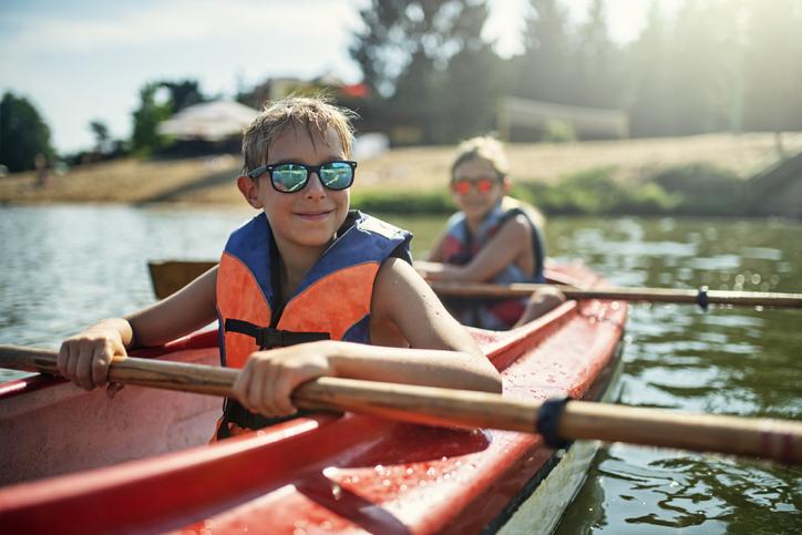 Two boys enjoying kayaking on lake on sunny summer day.