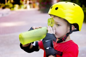 Child with roller skate helmet, drink a water.