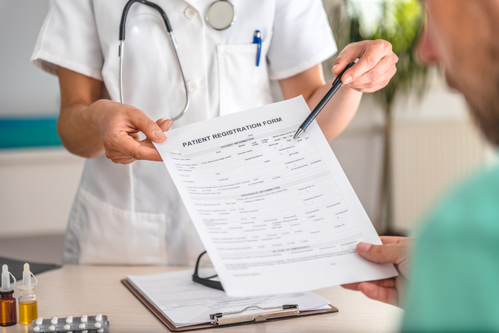 Doctor receiving patient registration form in hospital