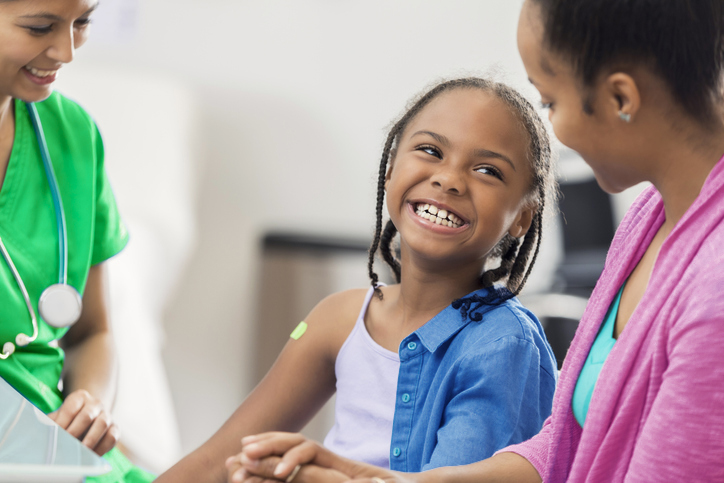 Cheerful African American elementary age girl receives an immunization from a nurse. The girl is sitting next to her mother.